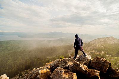 Caucasian hiker standing on rocky hilltop - p555m1414458 by Aleksander Rubtsov