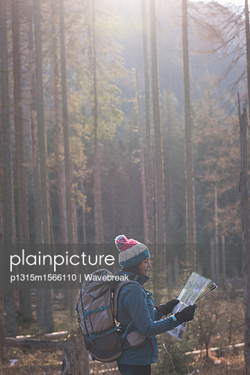 Female hiker looking at map on a sunny day - p1315m1566110 by Wavebreak