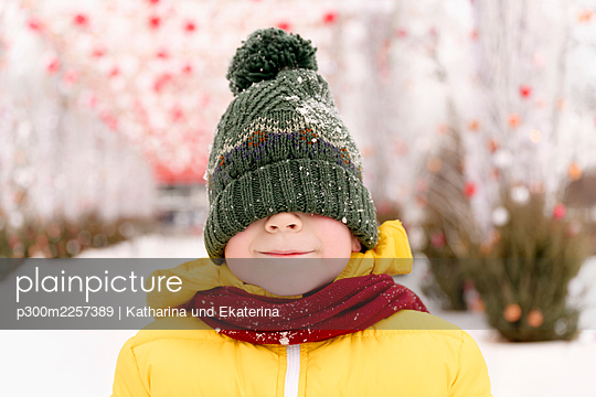 Boy hiding his face with knit hat - p300m2257389 by Katharina und Ekaterina