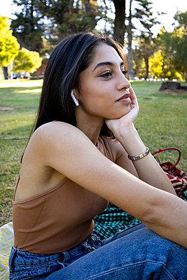 Teenager mit langen Haaren sitzt auf einer Picknickdecke im Park - p1640m2259878 von Holly & John