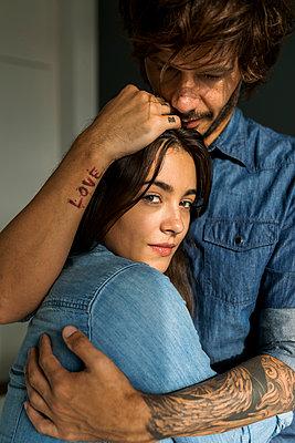 Tattooed man embracing girlfriend - p300m2059428 von Valentina Barreto