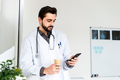 Male doctor holding disposable coffee cup while using smart phone in hospital - p300m2274653 by Giorgio Fochesato