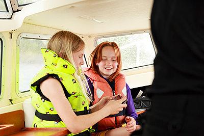 Smiling girls on boat - p312m2237390 by Phia Bergdahl