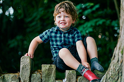Toddler putting on ankle boot in park - p429m2164643 by GS Visuals