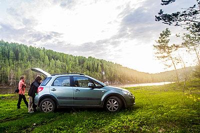 Caucasian tourists unloading car in remote landscape - p555m1414483 by Aleksander Rubtsov