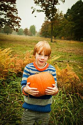 Junge hält Kürbis - p904m741700 von Stefanie Päffgen