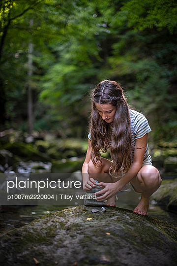 Teenage girl stacking stones in the forest - p1007m2220004 by Tilby Vattard