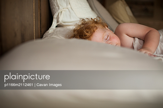 Close-up of cute baby boy sleeping on bed at home - p1166m2112461 by Cavan Images