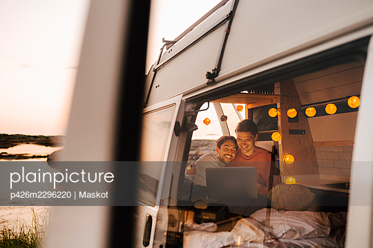 Smiling male friends using laptop seen through doorway of motor home - p426m2296220 by Maskot