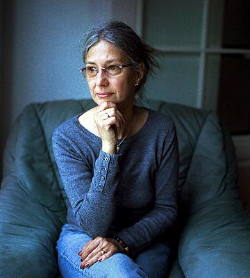 In einem Sessel sitzende Frau mittleren Alters - p1180m987345 von chillagano