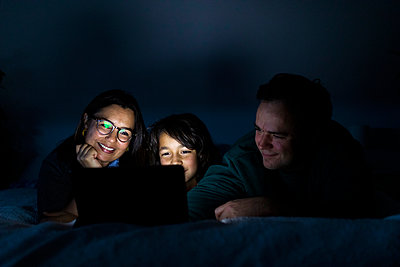 Parents and son lying together on bed at home using digital tablet - p300m2189535 by Valentina Barreto