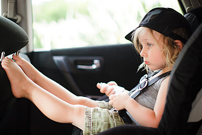Male toddler with feet up staring in back seat of car - p924m1422867 by Sasha Gulish