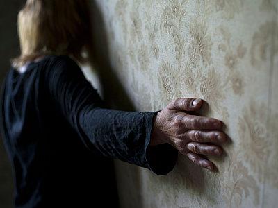 Frau berührt mit der Hand die Tapete - p945m1161610 von aurelia frey