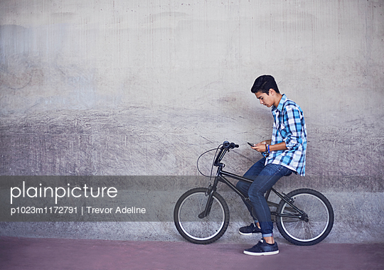 Teenage boy texting on BMX bicycle at wall