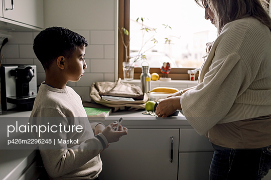 Son looking at mother while standing in kitchen - p426m2296248 by Maskot