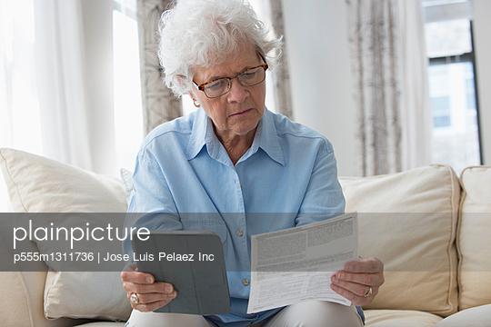 Older Caucasian woman using digital tablet to pay bills - p555m1311736 by Jose Luis Pelaez Inc