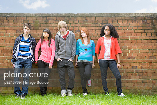 Teens standing by wall - p9248769f by Image Source