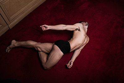 Bare-chested man poses on the floor - p1139m1503080 by Julien Benhamou