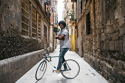 Spain, Barcelona, man standing with racing cycle in an alley - p300m2023740 von Josep Rovirosa
