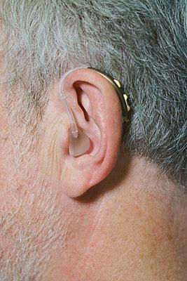 Cropped image of man wearing hearing aid - p301m1498509 by Halfdark