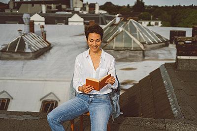 Frau liest gut gelaunt ein Buch auf Dach - p432m2185652 von mia takahara