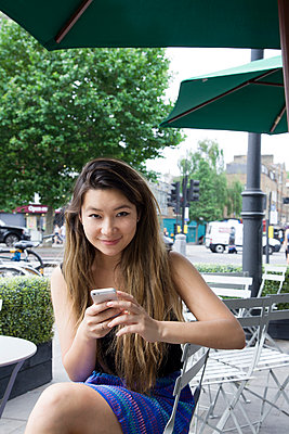 Asian woman using cell phone outdoors - p555m1410382 by verity jane smith
