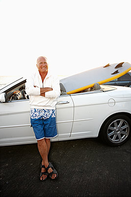 Caucasian man standing with car and paddleboard - p555m1480077 by Peathegee Inc