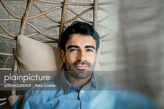 Young man resting on chair swing at cafe - p300m2286928 by Rafa Cortés