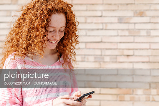 Cheerful redhead woman text messaging through smart phone in front of wall - p300m2287564 by COROIMAGE