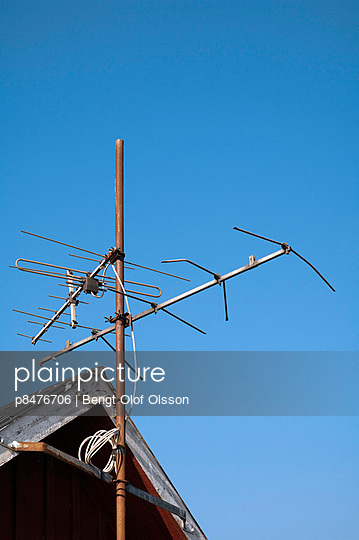 Cottage with old TV antenna against blue sky