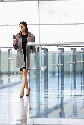 Businesswoman with smart phone walking in office corridor - p1192m2093851 by Hero Images