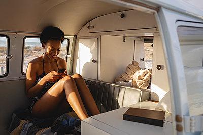 Beautiful woman using mobile phone in camper van at beach - p1315m2091163 by Wavebreak