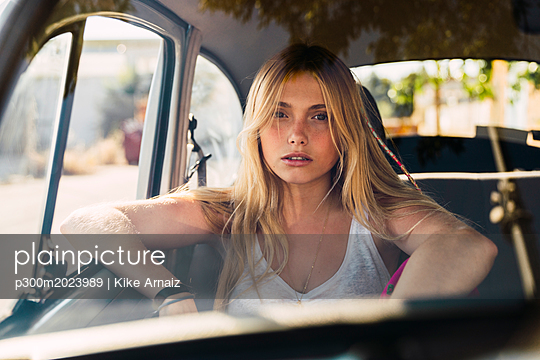 Portrait of young woman sitting in a car - p300m2023989 von Kike Arnaiz