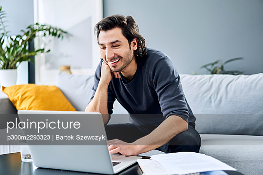 Smiling businessman with hand on chin using laptop at home - p300m2293323 by Bartek Szewczyk