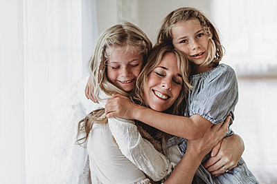 Daughters embracing smiling mother in natural light studio - p1166m2130876 by Cavan Images