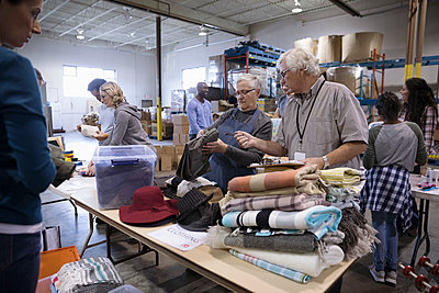Senior couple volunteers sorting clothing for clothing drive in warehouse - p1192m1517152 by Hero Images