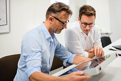Two businessmen examining solar panel on desk in office - p300m1563133 by Daniel Ingold