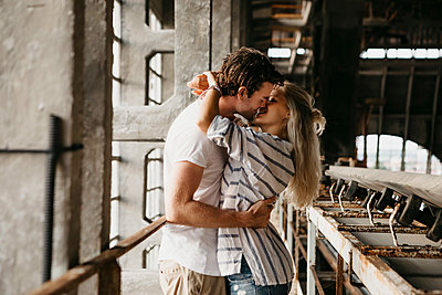 Young couple kissing in an old train station - p300m2104130 by letizia haessig photography
