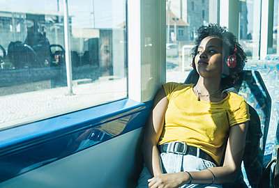 Young woman with headphones relaxing in a train - p300m2156734 by Uwe Umstätter