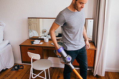 Mid adult man cleaning bedroom with vacuum cleaner - p426m2135687 by Maskot