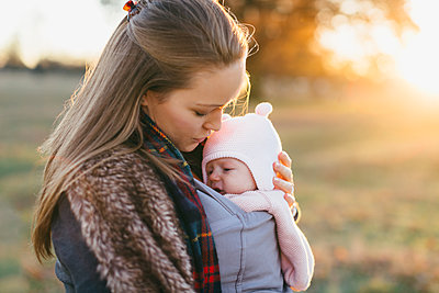 Mother and baby daughter outdoors, mother carrying baby in baby sling - p429m1557481 by Katie Rollings