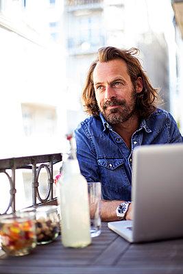 Mann mit Laptop auf Balkon - p788m1424699 von Lisa Krechting