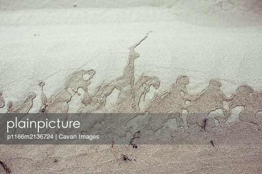 ocean water makes beautiful pattern on beach sand - p1166m2136724 by Cavan Images