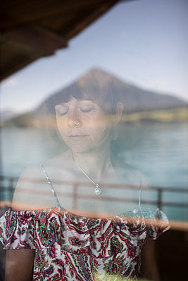Switzerland, Woman with closed eyes in front of a window - p1354m2272168 by Kaiser