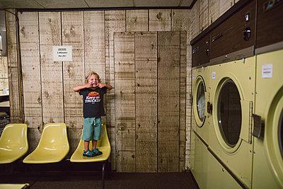 Kleiner Junge im Waschsalon - p1361m1332542 von Suzanne Gipson
