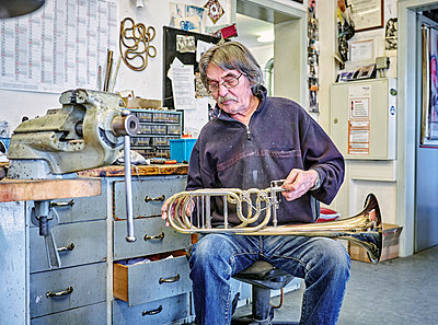 Instrument maker repairing trumpet in workshop - p300m1157204 by Dirk Kittelberger