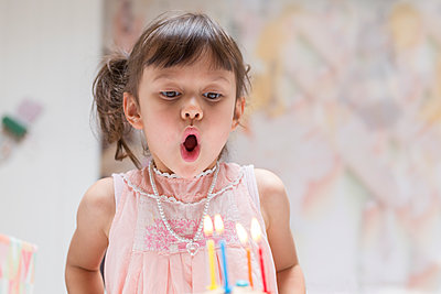 Portrait of little girl blowing out burning candles on her birthday cake - p300m2113984 by Stefan Rupp