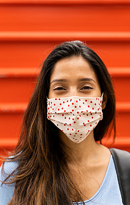 Smiling woman with protective face mask standing against shutter during COVID-19 - p300m2225000 by VITTA GALLERY