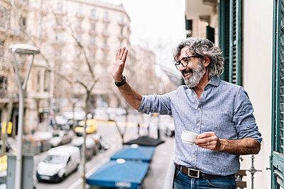 Cheerful senior man waving hand while having coffee in balcony of house - p300m2277137 by COROIMAGE