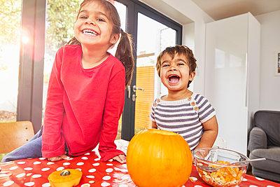Children carving pumpkin in kitchen - p429m2091536 by Sverre Haugland